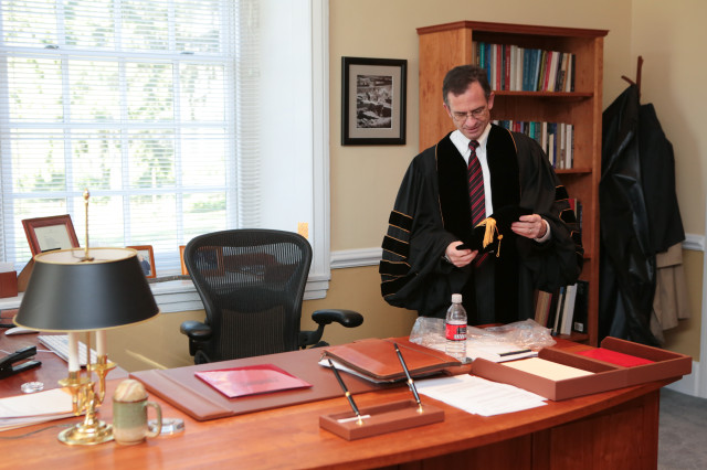 Weiss examines his cap in his office in Founders Hall.